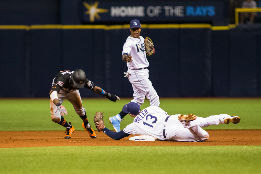 Brad Miller misses tag on Dee Gordon, but got him in a rundown./CARMEN MANDATO