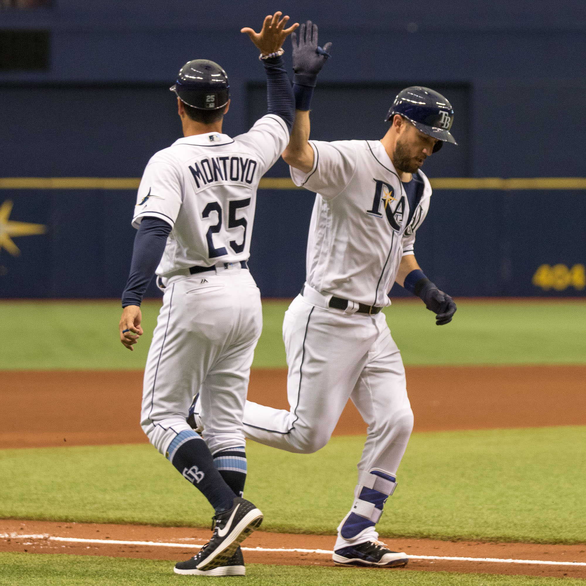 Plouffe high fives with Montoyo on his way to home plate./STEVEN MUNCIE