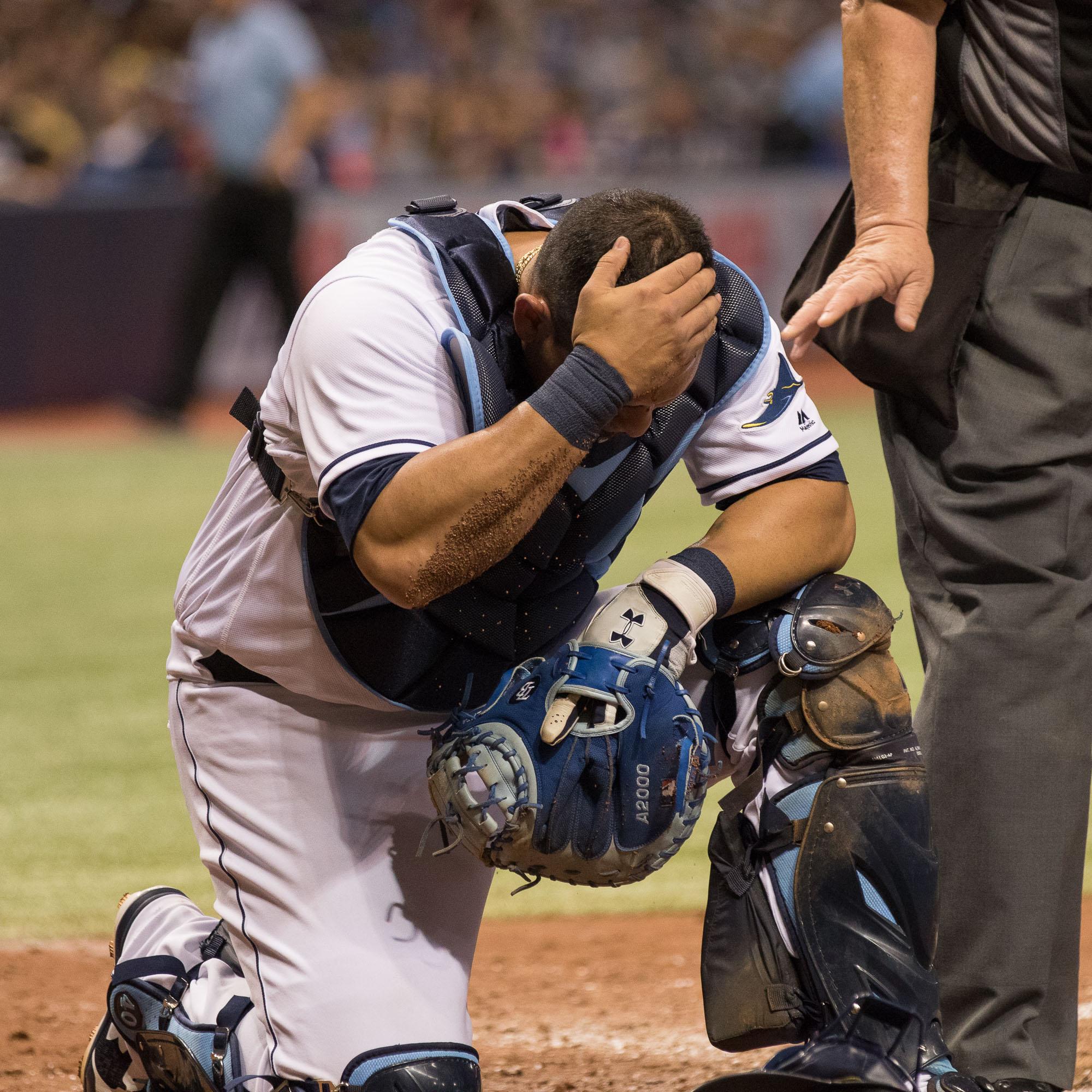 Wilson Ramos grabs his head in pain after getting hit with a broken bat./STEVEN MUNCIE