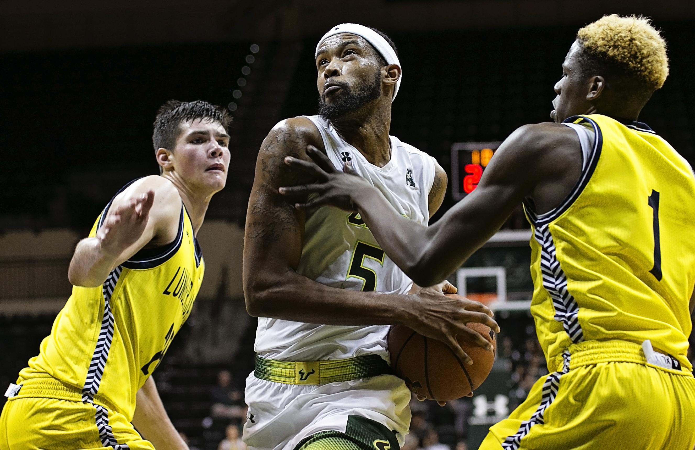 Martin splits two defenders for basket./CARMEN MANDATO